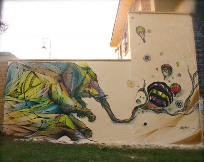 An elephant chases hot air balloons in this awesome street art painting by French graffiti artist Hopare