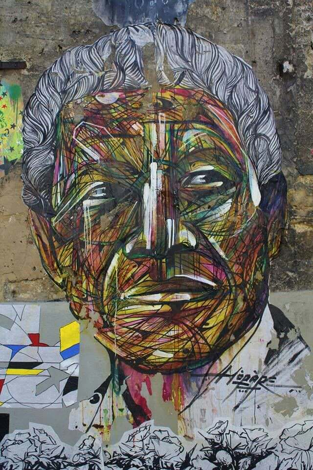 French graffiti artist Hopare paints a street art mural of Nelson Mandela in an artistic graphic style