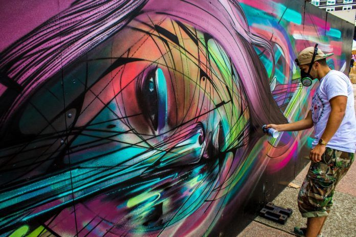 Street artist Hopare at work on one of his colorful graphic design influenced graffiti murals of a pretty girl