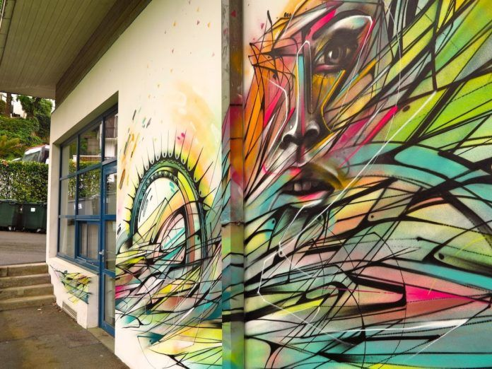 Tribal designs, abstract shapes and a portrait of a beautiful woman make up this street art mural by Hopare