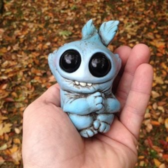 American artist Chris Ryniak holds on of his adorable palm sized monster dolls which has a cute smile and shiny eyes
