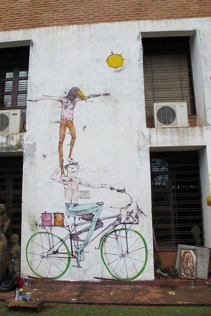 Mart Aire balances a bird headed man on a cyclist in this circus themed street art mural
