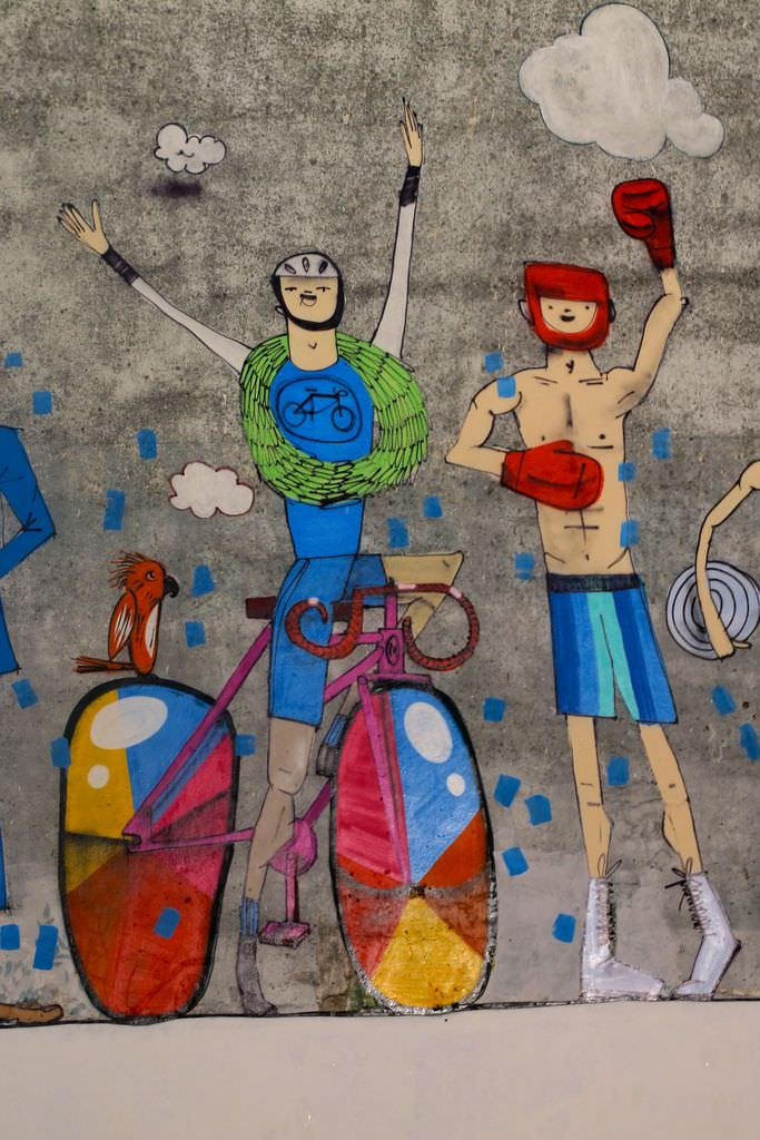 Mart Aire paints cheering athletes in this illustrative street art mural