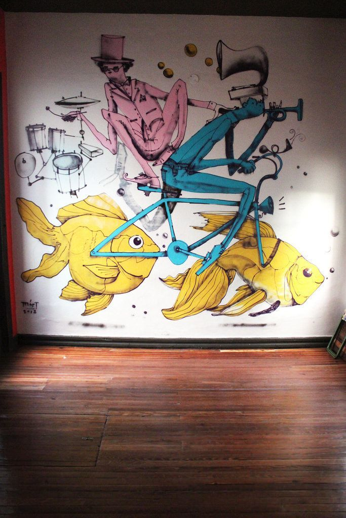 Musicians ride a bicycle with goldfish for wheels in this happy street art mural by Mart Aire