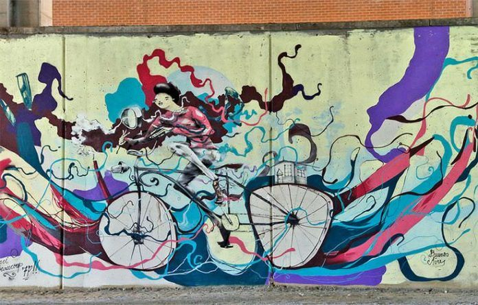 One of Mart Aire's street art cyclists rides through a swarm of creative swirls of color in this captivating graffiti mural