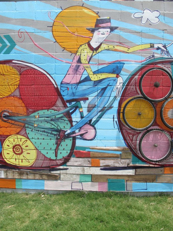Street artist Mart Aire creates a cheerful graffiti mural feeaturing a happy guy on a bicycle.