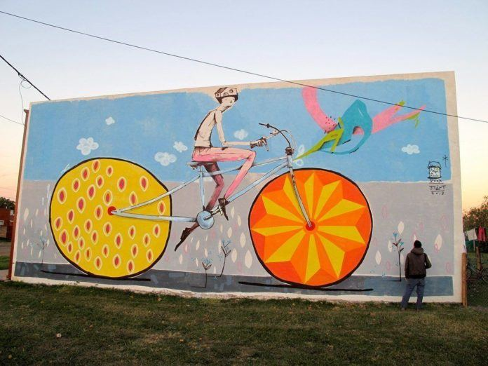 This huge street art mural by Mart Aire shows a cyclist carrying his home with him wherever he goes