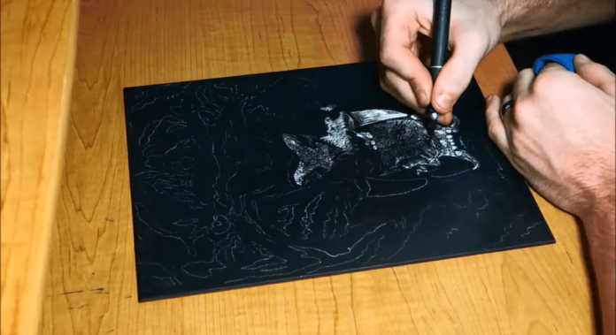 Mackenzie Streutker starts his art work with a black scratch board that he then carves out with a sharp blade. He has started with the tiger's teeth and lips.
