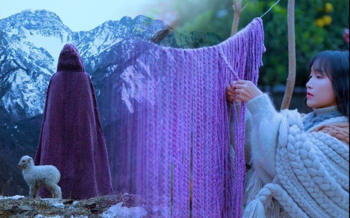 The purple cloak that Liziqui is making starts out as dozens of strands of yarn that have been draped over a line and cut into a crescent shape so that the artist can plait the strands while visualizing the finished cloak