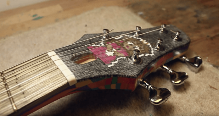 Princess Peach peeks out from between the tuning knobs on the head of the Super Mario guitar
